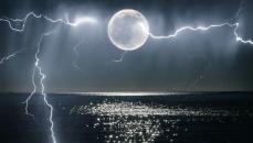 The moon glistening over the ocean with lightening in dark blue sky